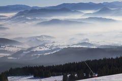 从滑雪的看法在Th的积雪和有雾的谷倾斜 库存照片