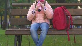 从热水瓶,快餐的女小学生饮用的茶在学校,健康食品以后的公园 股票视频
