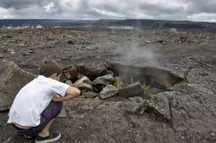 从熔岩漏洞出来的男孩注意的蒸汽。 库存图片