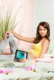 从片剂个人计算机的十几岁的女孩注意的照片 图库摄影