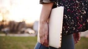 从牛仔裤的走通过有一个色的袋子和手中的膝上型计算机的公园的女孩的边的看法 关闭 股票视频