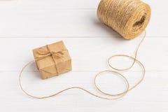 从牛皮纸的礼物在与螺纹的一张白色桌上 库存照片