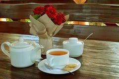 从猩红色玫瑰花束,白色茶壶的静物画 免版税库存照片