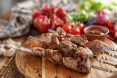 从猪肉和新鲜蔬菜的烤肉串在木背景 在开火烹调的开胃肉 图库摄影