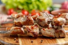 从猪肉的开胃烤肉串在开火烹调了 在木背景的静物画 图库摄影