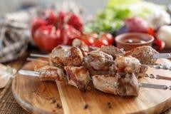 从猪肉的烤肉串 开胃肉在开火和新鲜蔬菜烹调了 土气 免版税库存图片