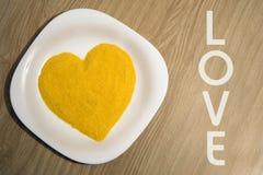 从玉米渣的黄色心脏形状 免版税库存照片