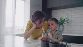 从玻璃玻璃的爱的美丽的母亲和儿子一起微笑的饮用的橙汁过去通过管 股票视频