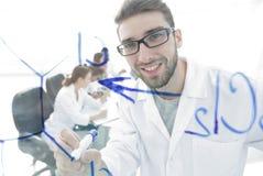 从玻璃的后面 科学家在玻璃委员会写一个标志 免版税图库摄影