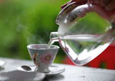从玻璃茶壶到茶杯里,室外的夏天的倾吐的热水 免版税图库摄影