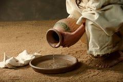 从瓶子的耶稣倾吐的水 免版税库存图片