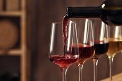 从瓶的倾吐的酒到玻璃里在地窖里 免版税库存图片