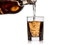 从瓶的威士忌酒倒在白色背景隔绝的小玻璃玻璃 免版税库存图片