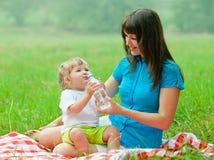从瓶的愉快的母亲和孩子饮用水 库存图片