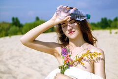 从瓶的美女饮用水在沙漠 库存图片
