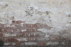 从用白色油漆从上面涂灰泥和盖的红砖的老墙壁 膏药在放消失了 库存图片