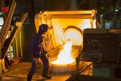 从电感应坩埚熔化炉取消炉渣 免版税库存图片