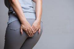 从痔疮的妇女拿着她的底部的痛苦和手,因为有胃肠痛苦 背景弄脏了关心概念表面健康防护屏蔽的药片 免版税库存图片
