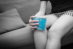 从痛苦的妇女痛苦在膝盖,使用解除cold-hot的组装在黑白口气的痛苦 背景弄脏了关心概念表面健康防护屏蔽的药片 免版税库存图片