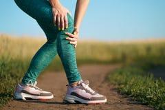 从痛苦的年轻女人痛苦在她的膝盖 免版税图库摄影