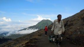 从登上伊真火山火山口的硫磺矿工 库存图片