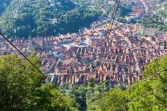 从登上坦帕电车的游人看的布拉索夫历史市中心 谷的中世纪镇-高尖顶和红色铺磁砖的 免版税库存照片
