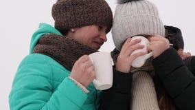 从白色玻璃的美丽的女孩饮料咖啡谈话,笑并且微笑 股票录像