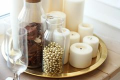 从白色蜡烛、透明小瓶和水晶玻璃的构成在窗口基石的一个金盘子立场 免版税库存照片