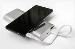 从白色powerbank的充电的智能手机 库存图片