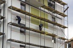 从的建筑场地视图与脚手架的工作者 免版税图库摄影