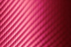 从皮革表面的抽象黑暗的桃红色背景 免版税库存图片