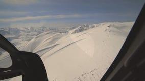 从直升机驾驶舱内部的鸟瞰图与飞行在冬天山峰的仪表盘的 影视素材