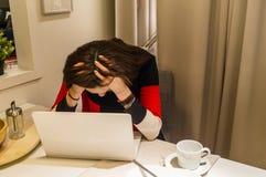 从研究的头疼膝上型计算机攻击了女孩 免版税库存照片