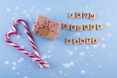 从秘密圣诞老人的礼物 有笔记的被包裹的礼物盒,在蓝色淡色背景的棒棒糖 库存图片