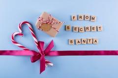 从秘密圣诞老人的礼物 有笔记、棒棒糖和桃红色的被包裹的礼物盒,上升了与弓的丝带在蓝色淡色背景 免版税图库摄影