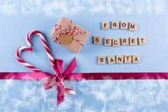 从秘密圣诞老人的礼物 有笔记、棒棒糖和桃红色的被包裹的礼物盒,上升了与弓的丝带在蓝色淡色背景 顶层 库存图片
