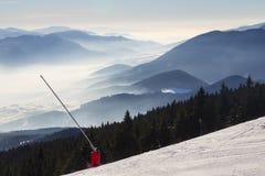 从积雪覆盖的滑雪倾斜的顶视图在薄雾包括谷 免版税库存照片