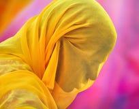 从穿在紫罗兰色背景的普斯赫卡尔的已婚妇女橙色围巾 免版税库存图片