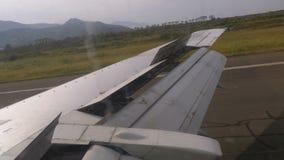 从窗口的看法在移动沿跑道的飞机的翼在机场在登陆以后 股票视频