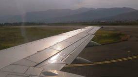 从窗口的看法在移动沿跑道的飞机的翼在机场在登陆以后 影视素材
