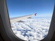 从窗口的看法在飞机和惊人美丽的云彩,照片第二的翼 库存图片