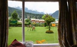 从窗口的绿色公园庭院视图在一个早晨好 免版税图库摄影