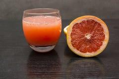 从粉红色葡萄柚的新近地被紧压的汁液在dar的一块玻璃 免版税库存图片