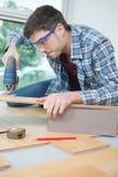 从粗纸板的聚集的家具使用无绳的螺丝刀 免版税库存图片