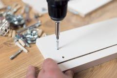 从粗纸板的聚集的家具,使用一把无绳的螺丝刀 免版税图库摄影