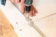 从粗纸板的聚集的家具,使用一把无绳的螺丝刀 库存照片