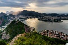 从糖面包山的里约热内卢视图在日落期间的城市 图库摄影