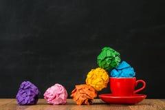 从红色咖啡杯的彩虹纸球 库存照片
