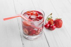 从红色莓果的刷新的水在木桌上的一块玻璃 自创鲜美和健康饮料 库存照片