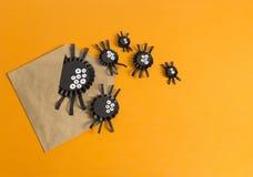 从纸的蜘蛛爬出信封 橙色背景 库存图片